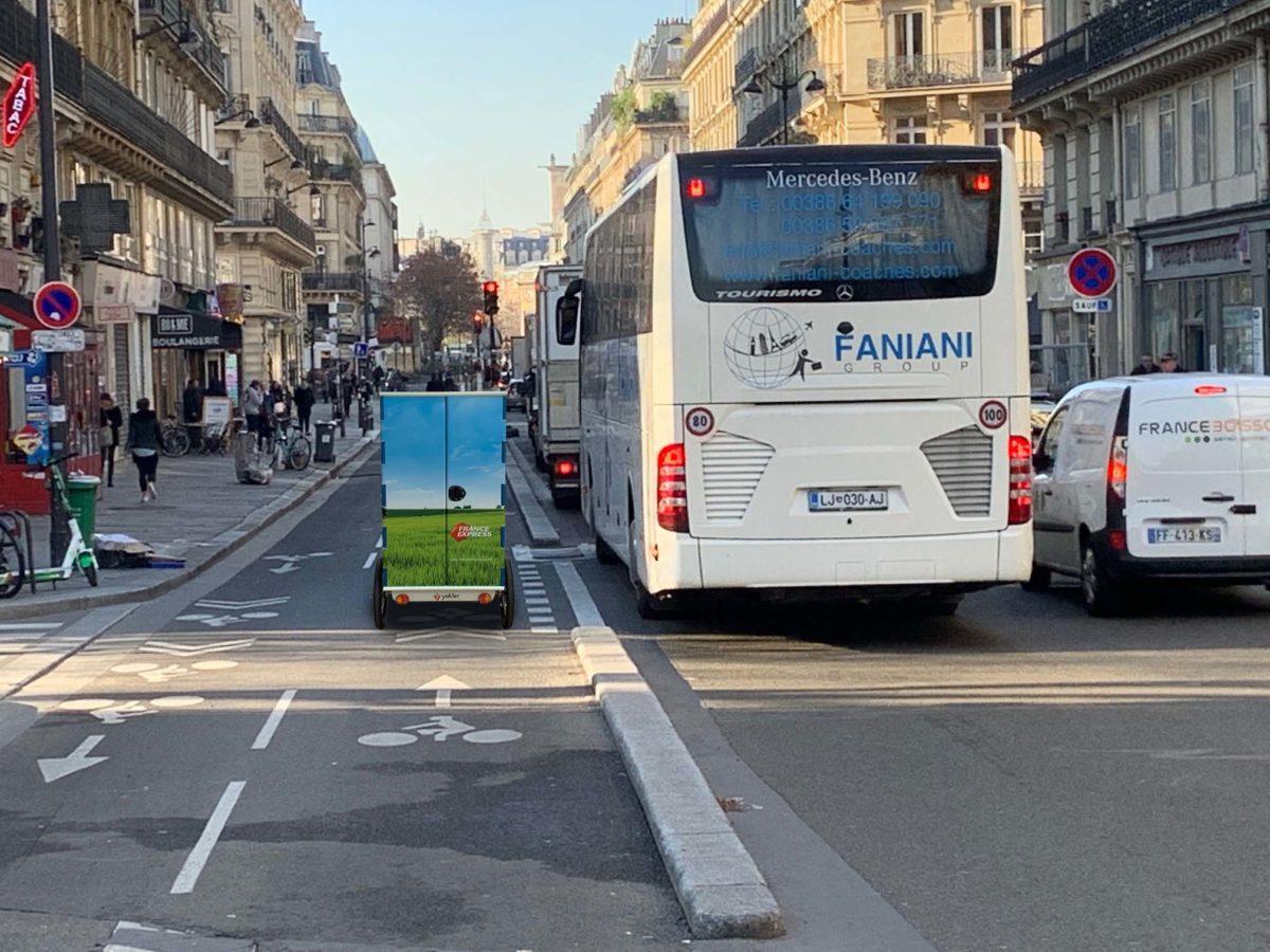 Triporteur électrique Yokler U circulant facilement sur la piste cyclable en site propre d'un boulevard parisien.